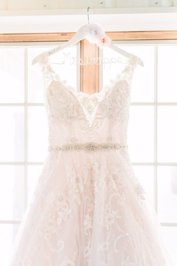Wedding dress hanging on custom hanger.  Ivory lace dress with beading  and belt.
