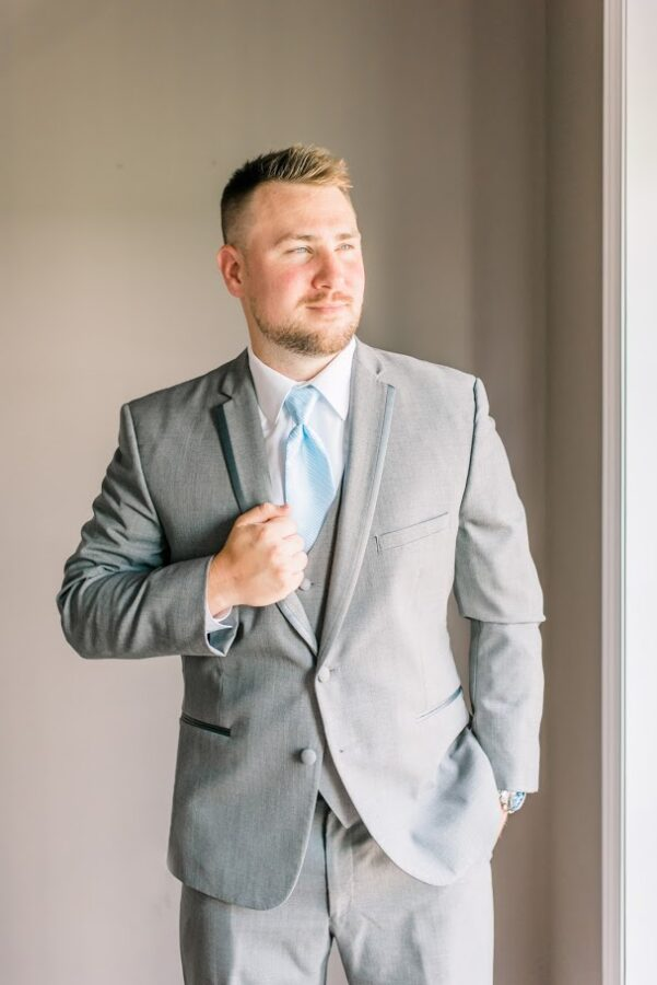 Groom on his wedding day in light grey tuxedo and light blue tie.
