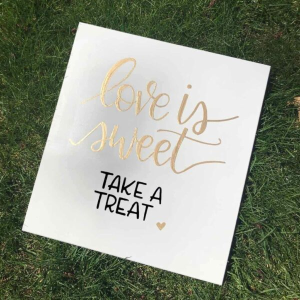 Simple sweet table sign with love is sweet take a treat written on it in handwritten lettering.