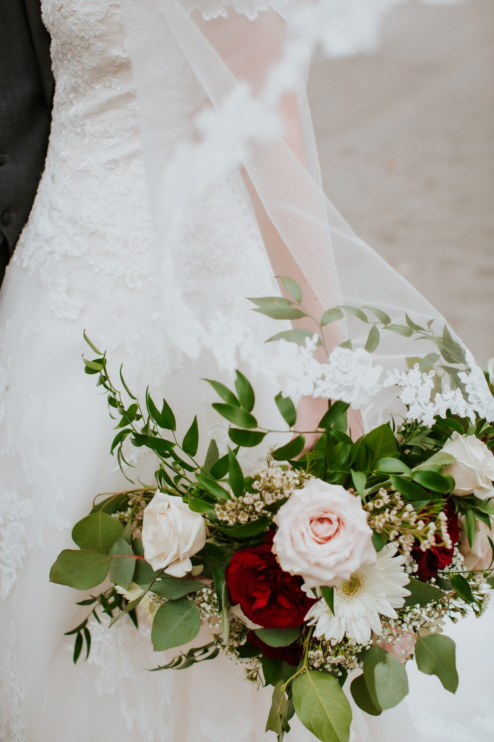 brides wedding bouquet with greenery and red
