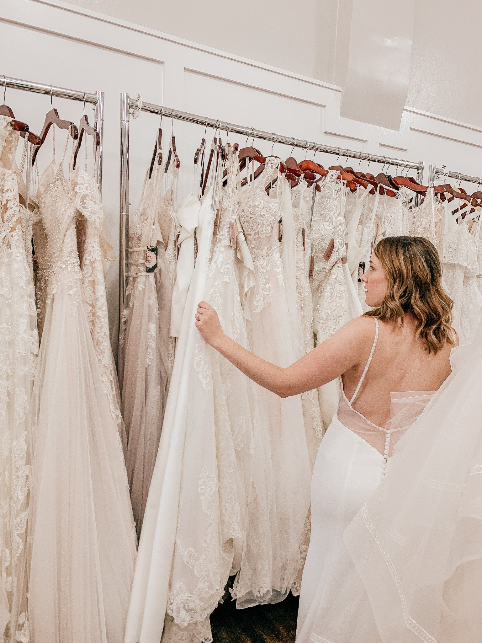 bride looking through wedding dresses to find her dream dress at a sample sale