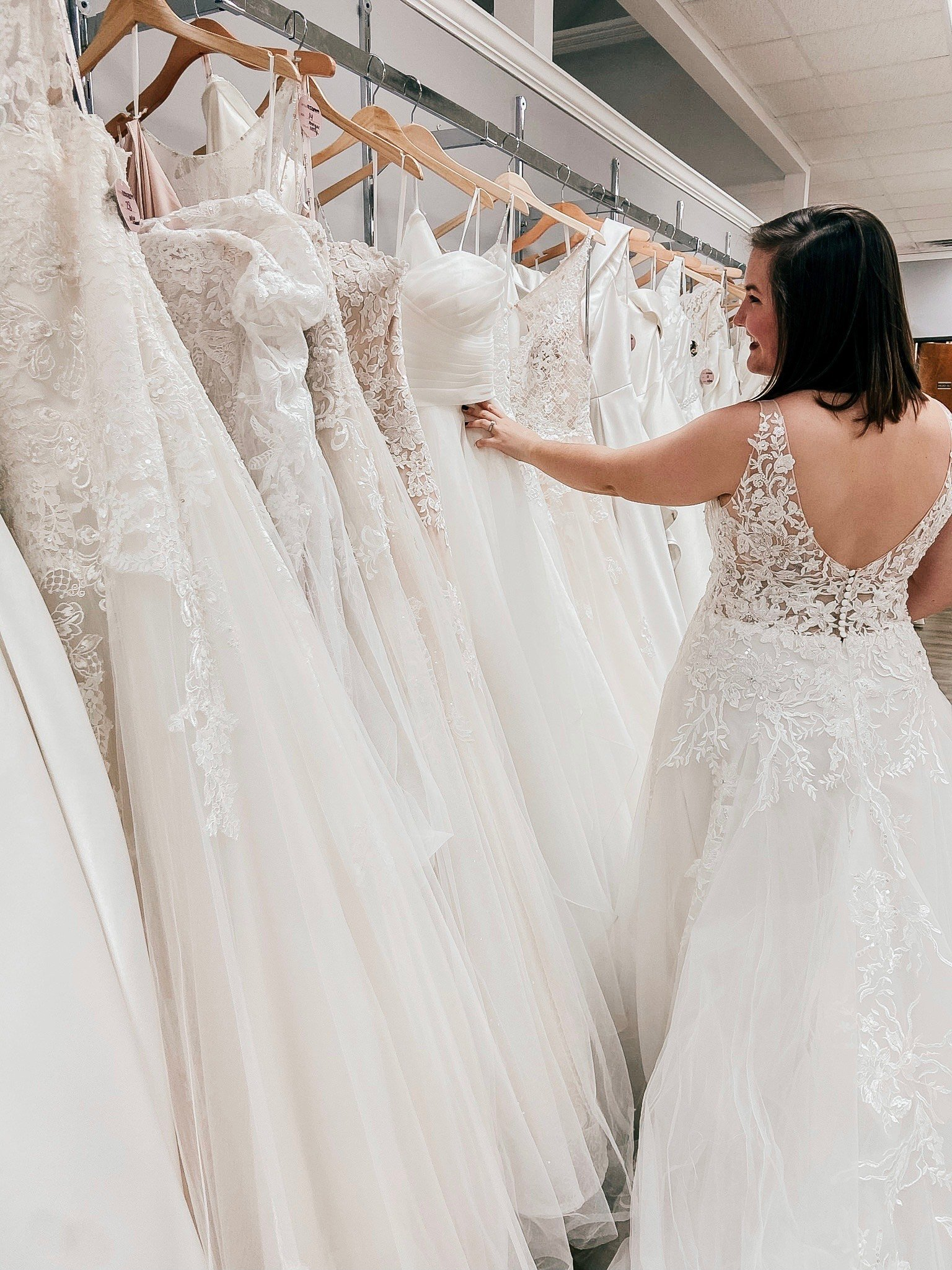 girl looking through dresses at a sample sale