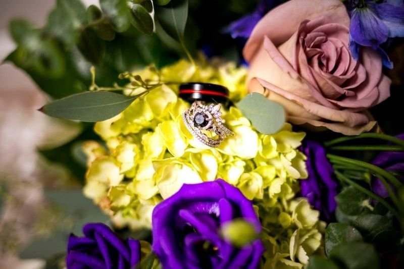 bride and grooms wedding rings in a bouquet of flowers