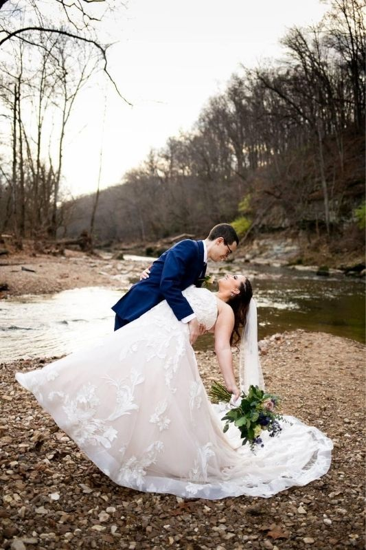 groom dipping bride with her flower bouquet