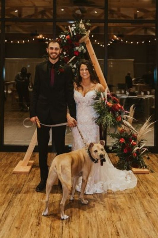 bride and groom with their dog on their wedding day