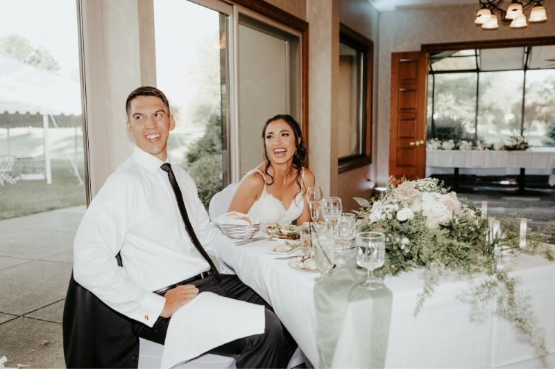 bride and groom laughing on their wedding day during the toasts with their family and friends