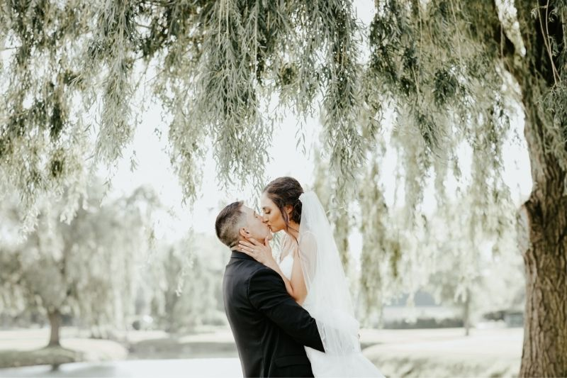 bride and groom kissing during wedding pictures