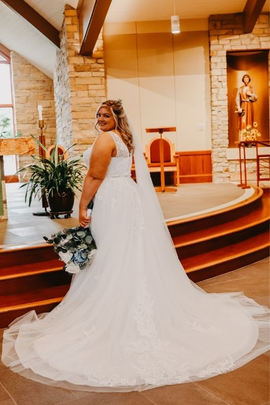 Bride turned around on her wedding day so you can see the back of her dress